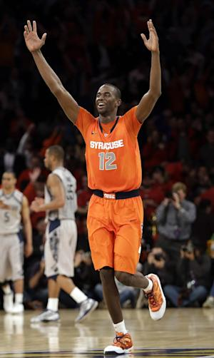 Syracuse's Baye Keita (12) celebrates after the overtime period of an NCAA college basketball game against the Georgetown at the Big East Conference tournament Friday, March 15, 2013, in New York. Syracuse won the game 58-55. (AP Photo/Frank Franklin II)
