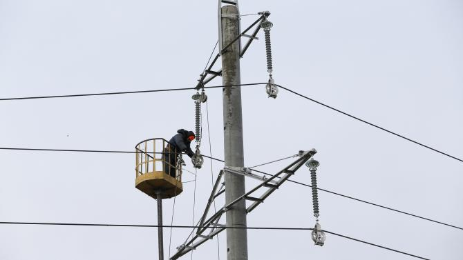 Worker repairs a power line damaged by recent shelling on the outskirts of Ukraine's town of Slavyansk