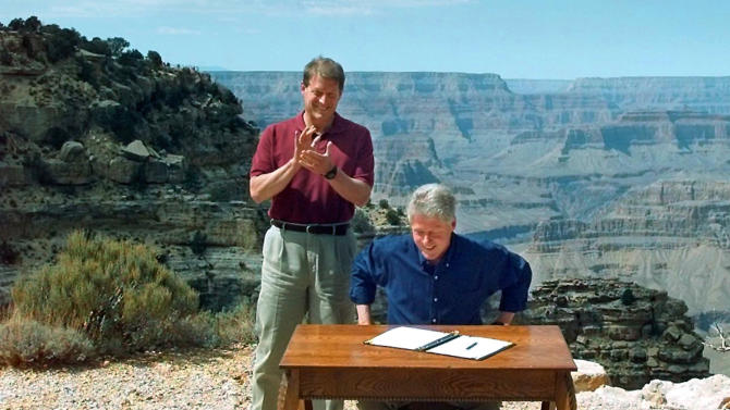 FILE - In this Sept. 18, 1996 file photo, Vice President Al Gore applauds after President Clinton signs a bill designating 1.7 million acres of land in southern Utah's red-rock cliffs as the Grand Staircase-Escalante National Monument. Some Western lawmakers are pushing for a showdown with Washington over federally-controlled land, picking a fight on an issue that they say puts an economic stranglehold on their states. Republican legislators in Utah and Arizona are leading a charge to hand over control of public territory that makes up much of the West, insisting local leaders could manage it better. (AP Photo/Doug Mills, File)