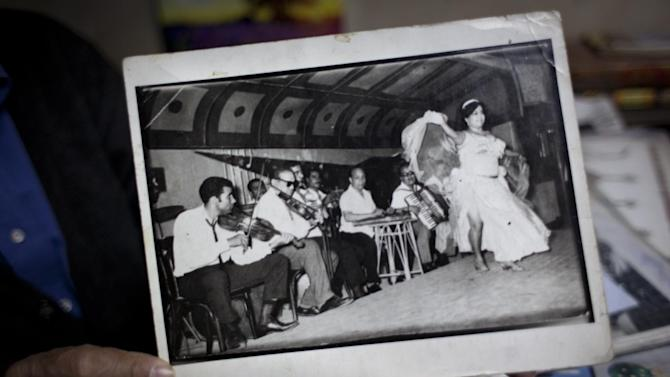 In this Wednesday, Jan. 2, 2013 photo,  Egyptian musician Abdul Rahman Marco displays a picture with him, at left, playing the violin during a show in 1959, at his music shop on Mohammed Ali street, a street modeled after Paris' boulevards and home to musicians, belly-dancers and instrument makers, in downtown Cairo, Egypt. The shops making, repairing and selling musical instruments that once packed the street are disappearing, along with their window displays of lute-like, stringed ouds, qanouns and tablas -- a drum made equally for the rapid-fire hand beats of belly-dance tunes or for the languid rhythms of a love ballad by Umm Kalthoum, the most famed singer of classical Arabic music. (AP Photo/Nasser Nasser)
