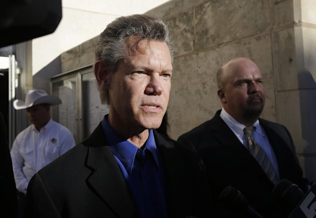 Entertainer Randy Travis, center, makes comments after exiting the Grayson County Courthouse with an unidentified person, right, Thursday, Jan. 31, 2013, in Sherman, Texas. Travis plead guilty to driving while intoxicated in a plea agreement with the court and will pay a $2,000 fine and serve a two year probation. (AP Photo/Tony Gutierrez)
