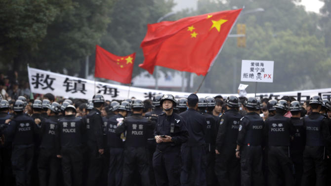 A Chinese police officer stands behind his folks confronting residents who gathered outside the government office in Zhejiang province's Ningbo city, during a protest against the proposed expansion of a petrochemical factory on Sunday, Oct. 28, 2012. Thousands of people in the eastern Chinese city clashed with police Saturday while protesting the plan that they say would spew pollution and damage public health, townspeople said. (AP Photo/Ng Han Guan)