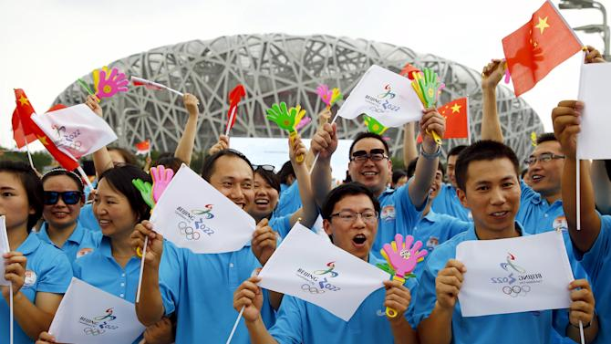 Participants holding Chinese national flags and Beijing 2022 Olympic flags cheer, ahead of IOC's announcement of the winner city for the 2022 winter Olympics bid, outside the Birds' Nest, also known as the National Stadium, in Beijing