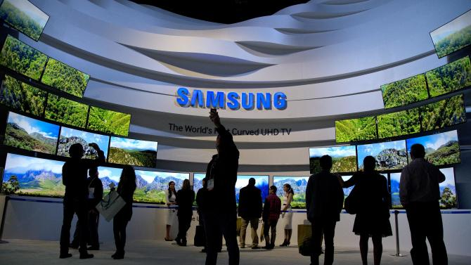 FILE - In this Thursday, Jan. 9, 2014, file photo, trade show attendees take in a display of Samsung curved UHD TVs at the International Consumer Electronics Show, in Las Vegas. Samsung reports quarterly earnings on Friday, Jan. 24, 2014.(AP Photo/Julie Jacobson, File)