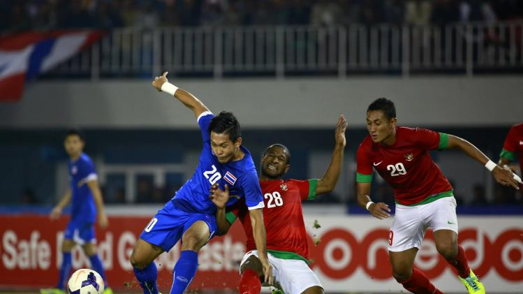 Pombubpha of Thailand challenges Ibo of Indonesia during their men's final soccer match at 27th SEA Games in Naypyitaw