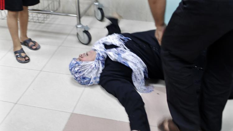 Palestinian mother lies on ground as she mourns death of son, who medics said was killed by Israeli shelling, at a hospital in Gaza City
