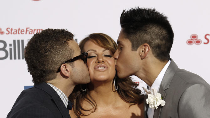 FILE - In this April 26, 2012, file photo, Singer Jenni Rivera, center, is kissed by singers Nacho, left, and Chino, right, as they walk the red carpet at the Latin Billboard Awards in Coral Gables, Fla. The wreckage of a small plane believed to be carrying Mexican-American music superstar Jenni Rivera was found in northern Mexico on Sunday, Dec. 9, 2012, and there are no apparent survivors, authorities said.  (AP Photo/Wilfredo Lee, file)