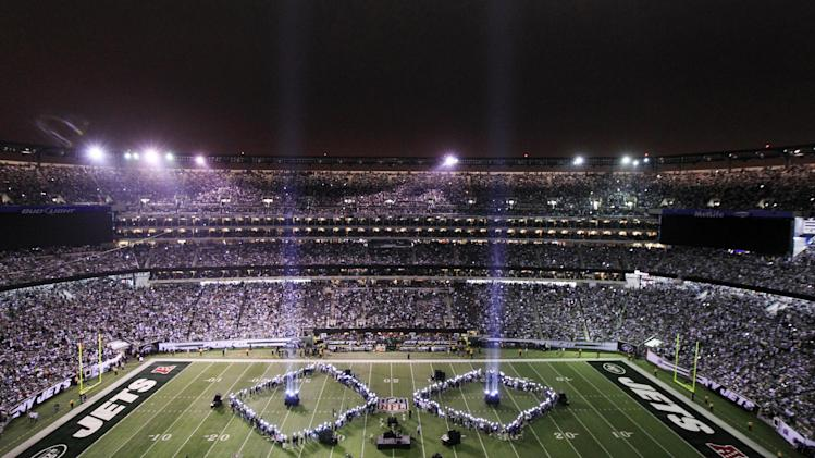 Beams of light rise towards the sky as part of the half time show marking the September 11 anniversary at an NFL football game between the New York Jets and Dallas Cowboys on Sunday, Sept. 11, 2011,  in East Rutherford, N.J. (AP Photo/Julio Cortez)