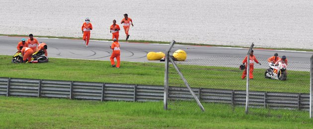 Italy's rider Marco Simoncelli lies on the racetrack after a crash involving Simoncelli, Valentino Rossi of Italy and Colin Edwards of the US,  at the Malaysian MotoGP Grand Prix in Sepang, Malaysia,