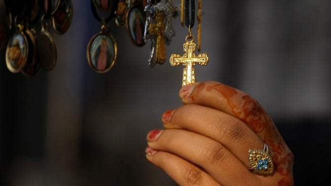 A Pakistani Christian girl buys a cross at a shop outside a local church on Christmas Day in Peshawar, Pakistan, Thursday, Dec. 25, 2014. (AP Photo/Mohammad Sajjad)