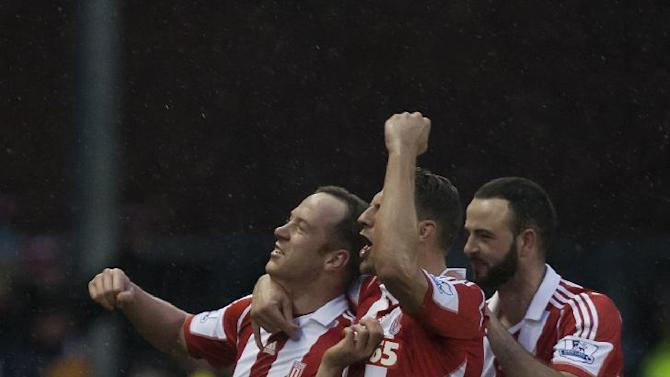 Stoke's Charlie Adam, left, celebrates with teammates Erik Pieters, centre, and Marc Wilson after scoring his second goal against Manchester United during their English Premier League soccer match at the Britannia Stadium, Stoke, England, Saturday Feb. 1, 2014