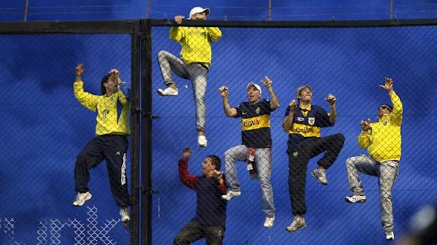 Boca Juniors' fans climb a fence during an Argentine First Division soccer match against River Plate in Buenos Aires (Reuters)