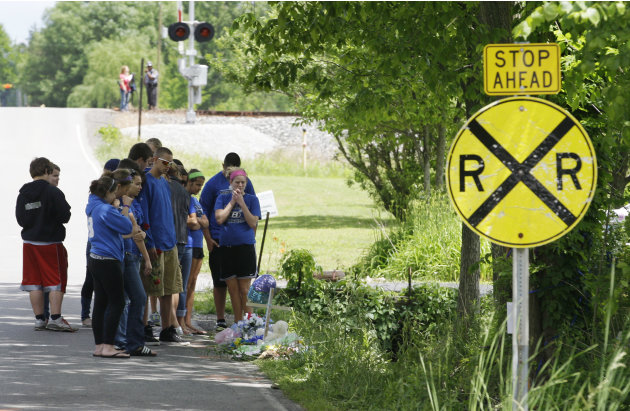 Brunswick High School students console each other at a car crash site Monday, June 4, 2012, near Brunswick, Ohio. A fourth victim of the crash, Kevin Fox, died Monday, a day after he was thrown from a