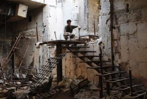 A Free Syrian Army fighter sits atop a flight of stairs…