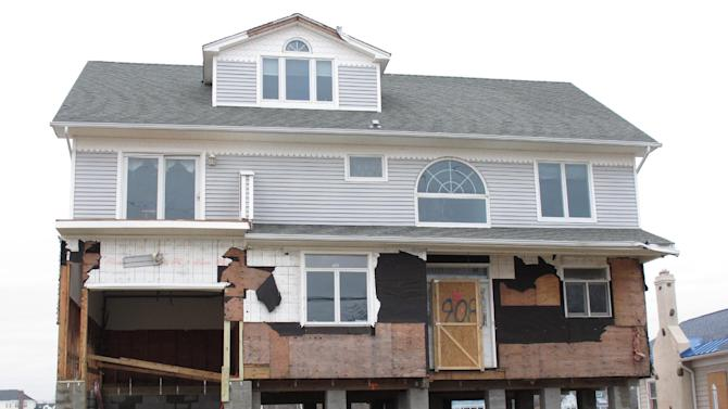 This house in Sea Bright, N.J., shown here on Jan. 15, 2013, is one of the first in the storm-devastated town to be elevated while being rebuilt. The town's entire business district was wiped out by Superstorm Sandy (four shops have since re-opened) and 75 percent of residents are still homeless. Yet Sea Bright is determined to rebuild as a debate rages on whether to restore shore communities to their pre-storm condition, or buy out properties in flood-prone areas and depopulate them. (AP Photo/Wayne Parry)