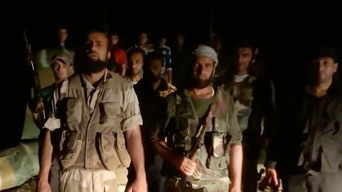In this Sunday, May 5, 2013 image taken from video obtained from the Shaam News Network, which has been authenticated based on its contents and other AP reporting, men stand near a wrecked helicopter, left, in Deir el-Zour, Syria. Syrian rebels shot down a military helicopter in the country's east, killing eight government troops on board a day after opposition forces entered a sprawling military air base in the north, activists said Monday. (AP Photo/Shaam News Network via AP video)