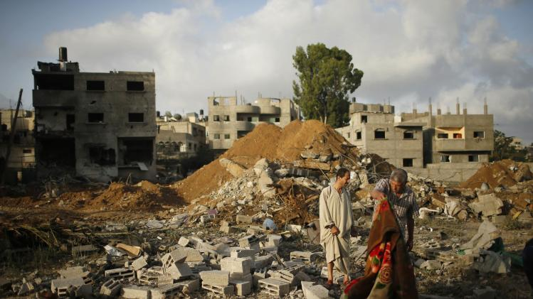Palestinians stand amongst the rubble of Tayseer Al-Batsh's family house, which police said was destroyed in an Israeli air strike in Gaza City