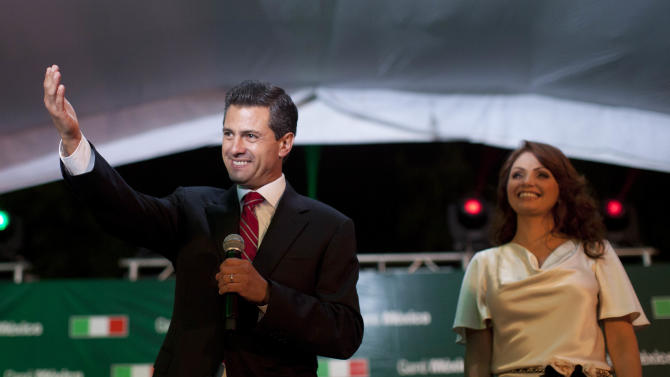 Enrique Pena Nieto, presidential candidate for the Revolutionary Institutional Party (PRI), left, speaks to supporters accompanied by his wife Angelica Rivera at the party's headquarters in Mexico City, early Monday, July 2, 2012. Mexico's old guard sailed back into power after a 12-year hiatus Sunday as the official preliminary vote count handed a victory to Pena Nieto, whose party was long accused of ruling the country through corruption and patronage. (AP Photo/Alexandre Meneghini)