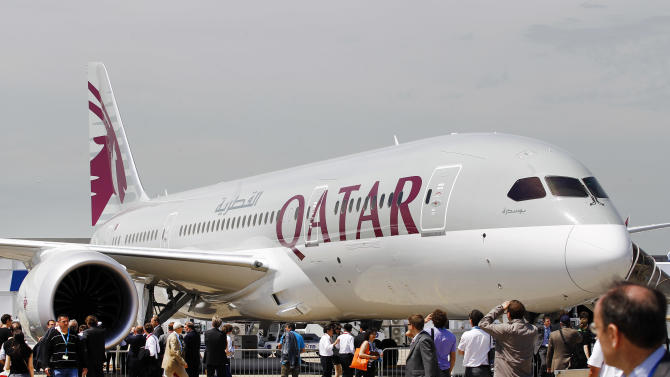 Visitors walk near a Qatar Airways Boeing 787 Dreamliner, on the first day of the Paris Air Show at Le Bourget airport, north of Paris, Monday June 17, 2013. (AP Photo/Remy de la Mauviniere)