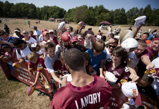 Washington Redskins fans gather for autographs from safety LaRon Landry during the NFL football team's training camp practice on Monday, Aug. 1, 2011, in Ashburn, Va. The lockout. The heat. The losing. Whatever the reasons, the crowds are unusually sparse so far at Redskins training cam practices. (AP Photo/Evan Vucci)