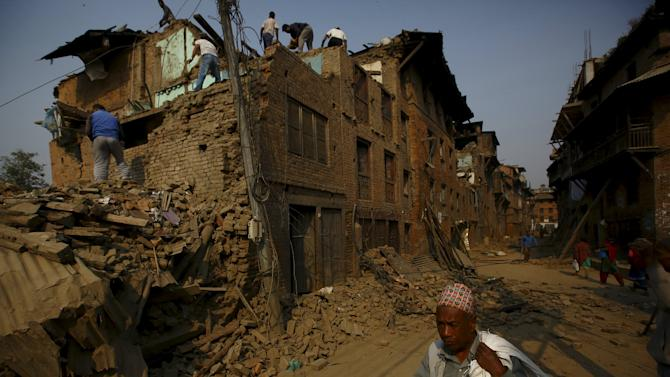 A man carrying goods walks past collapsed houses after the April 25 earthquake at Bhaktapur