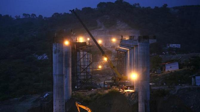 Labourers work at the construction site of a highway bridge on the outskirts of Jammu August 30, 2013. REUTERS/Mukesh Gupta