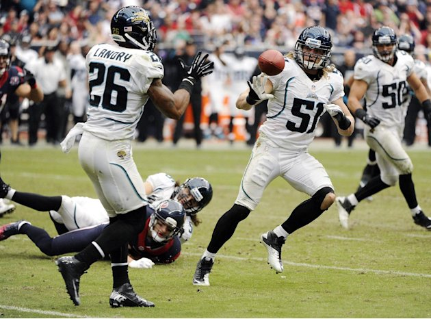 Jacksonville Jaguars' Paul Posluszny (51) tosses the ball to Dawan Landry (26) after intercepting a pass from the Houston Texans during the fourth quarter of an NFL football game, Sunday, Nov. 18, 201