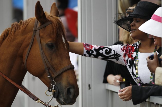 Race-goers pet a track marshall's horse before the 138th running of the Preakness Stakes at Pimlico Race Course in Baltimore