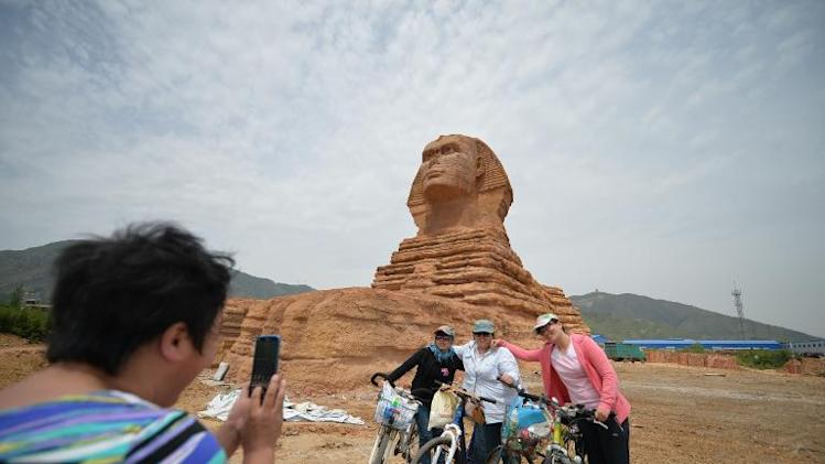 Residents pose for a photo before a full-size replica of the Great Sphinx of Giza in Donggou village in Shijiazhuang, north China's Hebei province on May 13, 2014
