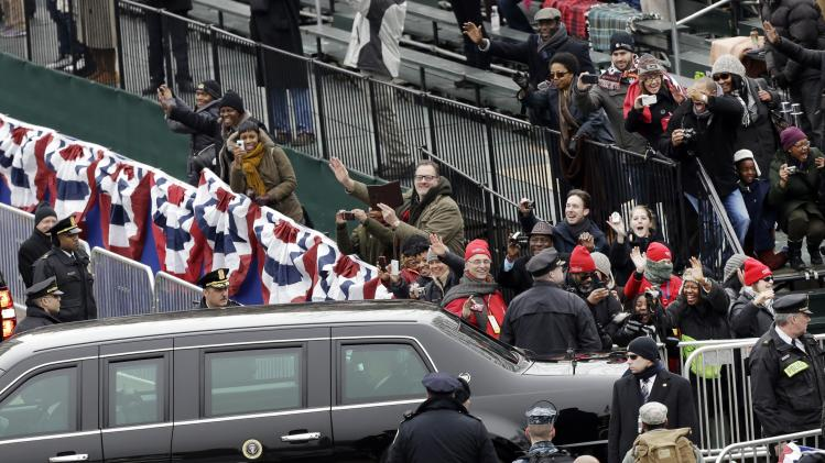 People wave at President Barack Obama and Vice President Joe Biden as their limousine passes Monday, Jan. 21, 2013, in Washington.  (AP Photo/Charlie Neibergall )