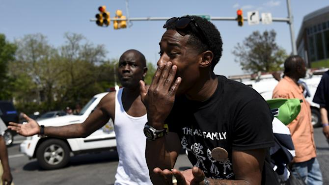 A man reacts to the effects of pepper spray just deployed by law enforcement officers at the intersection of North and Pennsylvania Avenues in Baltimore