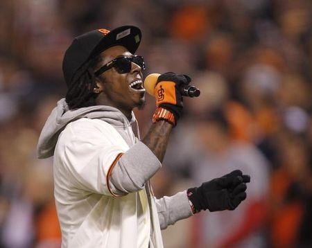 Rapper Lil Wayne sings during the seventh inning stretch in Game 6  of the MLB NLCS playoff baseball series between the St. Louis Cardinals and the San Francisco Giants in San Francisco