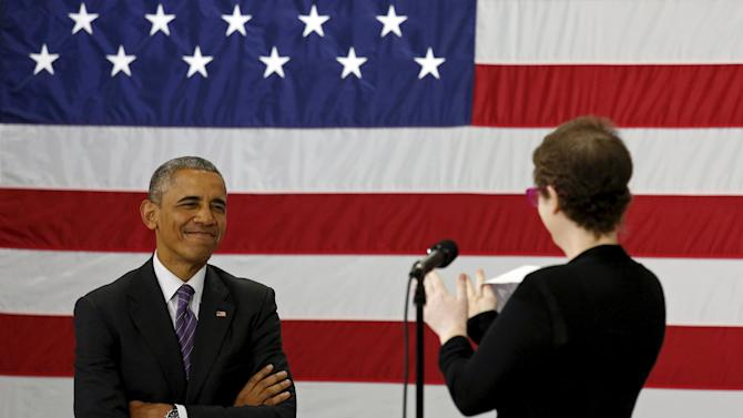 U.S. President Barack Obama receives applause from Kelly Bryant as she introduces him to speak about the Affordable Care Act during a visit to Taylor Stratton Elementary School in Nashville
