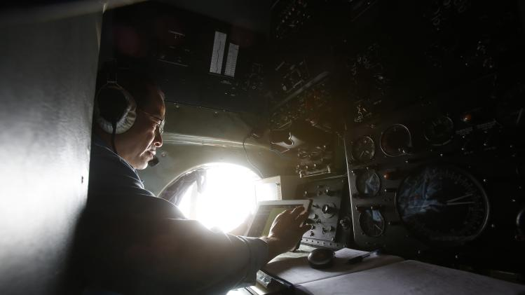 Military officer Duong Van Lanh works onboard a Vietnamese airforce AN-26 during a mission to find the missing Malaysia Airlines flight MH370 off Tho Chu islands