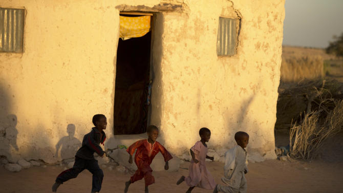 In this Nov. 1, 2012 photo, seven-year-old Achta, second right, plays with Nasruddin, right, Mahamat, second left, and her big brother, in front of her family's one-room house in Louri village, in the Mao region of Chad. Achta's birth seven years ago coincided with the first major drought to hit the Sahel this decade. Climate change has meant that the normally once-a-decade droughts are now coming every few years. The droughts decimated her family's herd. With each dead animal, they ate less. (AP Photo/Rebecca Blackwell)