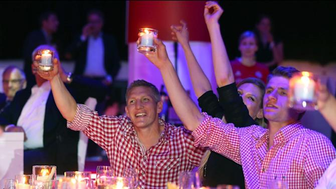 In this picture taken Saturday May 10, 2014, Bayern Munich soccer players Bastian Schweinsteiger, left and Thomas Mueller, right, celebrate during the official Champions party  in Munich , Germany