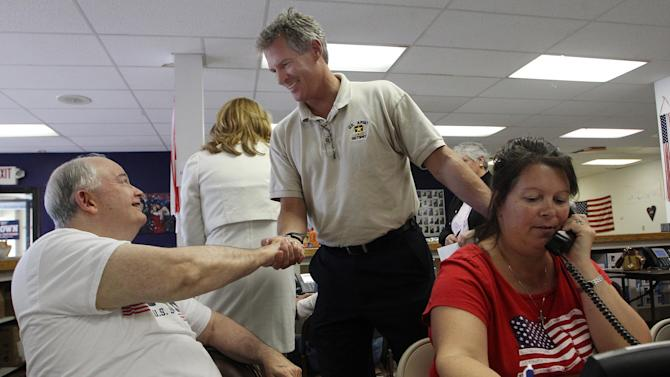 Scott Brown, a former U.S. Senator from Massachusetts, greets volunteers at his campaign headquarters Tuesday Sept. 9, 2014, in Manchester, N.H. Brown moved to New Hampshire and is seeking the Republican party nomination for U.S. Senate hoping to unseat Democrat Jeanne Shaheen.(AP Photo/Jim Cole)