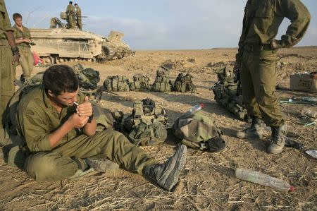 An Israeli soldier smokes a cigarette after crossing back into Israel from Gaza