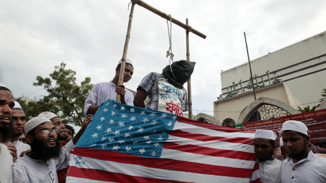 """Bangladeshi Muslims gather around a mock hangman's noose with a man representing the director of the film """"Innocence of Muslims"""" during a protest in Dhaka, Bangladesh, Friday, Sept. 21, 2012. The protest was against the anti-Islam film that ridicules Islam's Prophet Muhammad. The writing reads 'hang the notorious Bacile'. (AP Photo/A.M. Ahad)"""