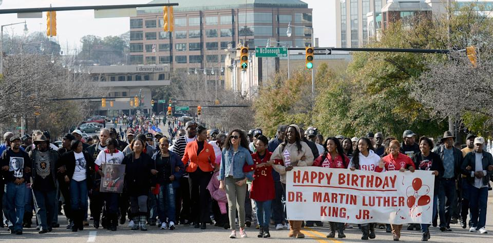 Participants walk with arms linked up Dexter Avenue in Montgomery, Ala., during a Martin Luther King march on  Monday, Jan. 21, 2013. (AP Photo/AL.com, Julie Bennett)