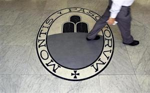 Man walks on a logo of the Monte Dei Paschi Di Siena bank in Rome