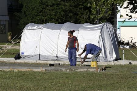 Men work near a tent of a field hospital set up for training purposes, in the Pedro Kouri Tropical Medicine Institute, where Cuban doctors train for their Ebola mission, in Havana