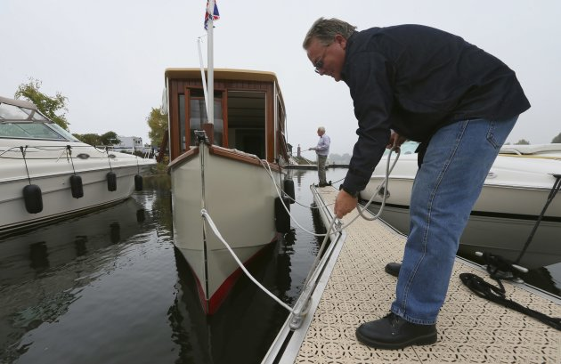 Semi-retired Ian Morton (R) helps Peter Lenihan tie down his houseboat at Le Port De Plaisance de Lachine, a marina in Montreal, Quebec, October 4, 2012. There are no good statistics on just how many boomers are taking retirement on the road. But some indicators - steadily rising traffic at houseboat and recreational vehicle websites, and a growing number of retirement-age members on couchsurfing.com - confirm the trend. Picture taken October 4, 2012.       To match Feature RETIREMENT-TRAVELING/       REUTERS/Christinne Muschi (CANADA - Tags: BUSINESS SOCIETY)