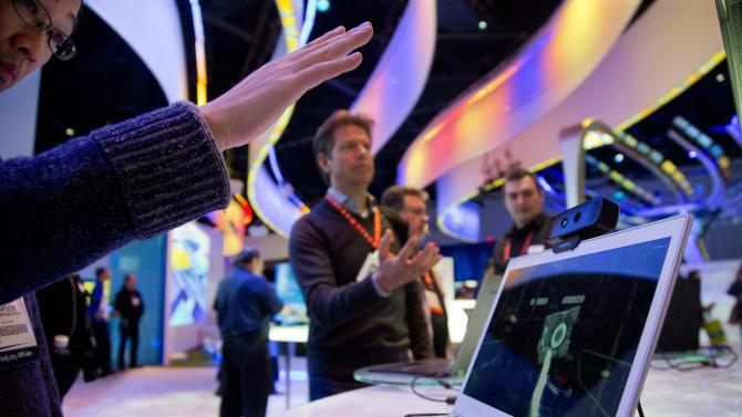 Convention attendees test out Intel's Creative Interactive Gesture Camera development kit at the Consumer Electronics Show, Friday, Jan. 11, 2013, in Las Vegas. (AP Photo/Julie Jacobson)