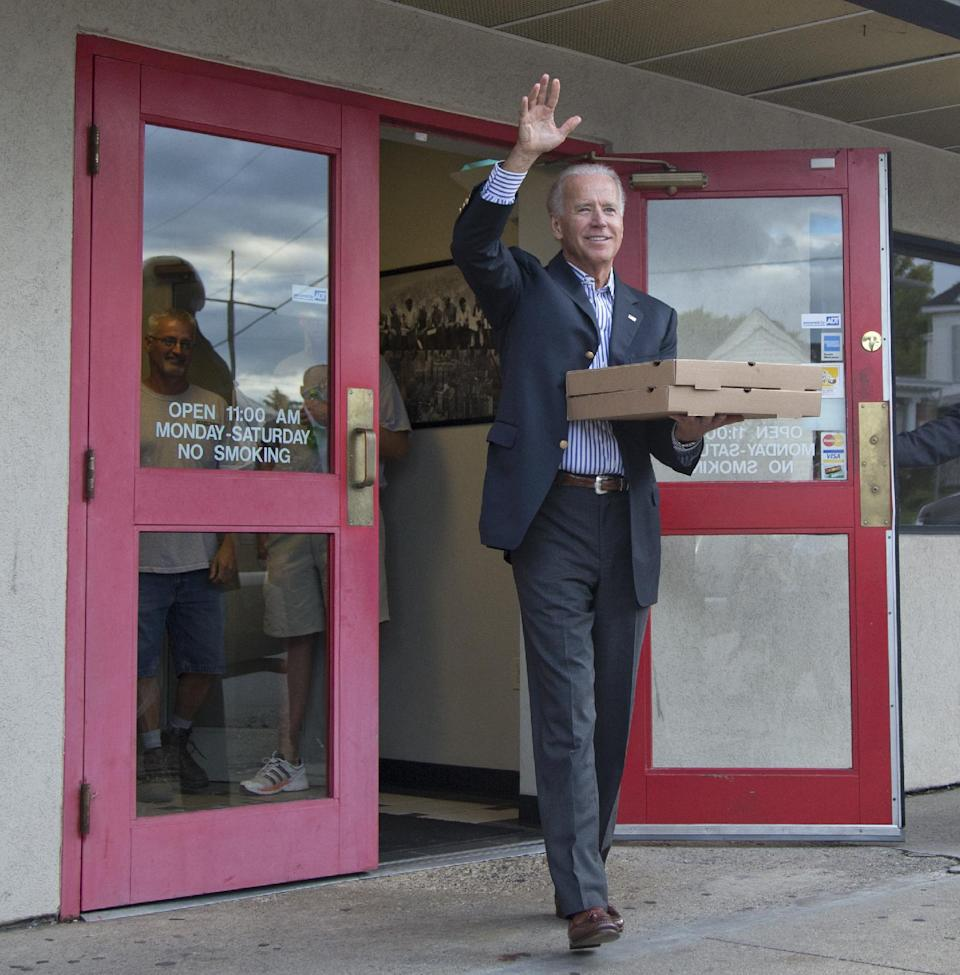Vice President Joe Biden exits Cardo's Pizza Restaurant with pizza in hand after greeting patrons, Saturday, Sept. 8, 2012, in Jackson, Ohio.  (AP Photo/Carolyn Kaster)