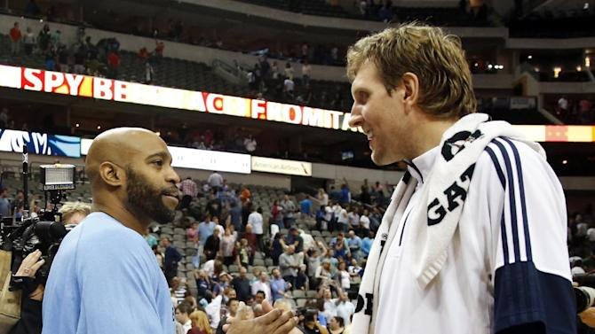 Former teammates, Memphis Grizzlies' Vince Carter, left, and Dallas Mavericks' Dirk Nowitzki of Germany greet each other after their preseason NBA basketball game, Monday, Oct. 20, 2014, in Dallas. The Mavericks won 108-103. (AP Photo/Tony Gutierrez)