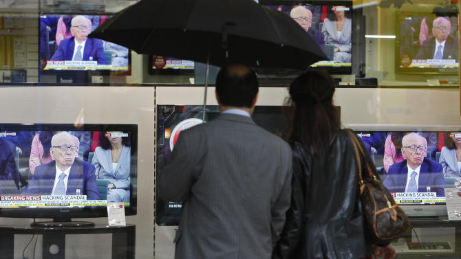 Pedestrians look at television screens, showing Chairman of News Corporation Rupert Murdoch during a select committee on the phone hacking scandal, outside a electronics shop in London, Tuesday, July 19, 2011. (AP Photo/Akira Suemori)