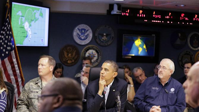 President Barack Obama, center, attends a briefing with Federal Emergency Management Agency administrator Craig Fugate, right, at the National Response Coordination Center at FEMA Headquarters in Washington, on Sunday, Oct. 28, 2012. (AP Photo/Jacquelyn Martin)