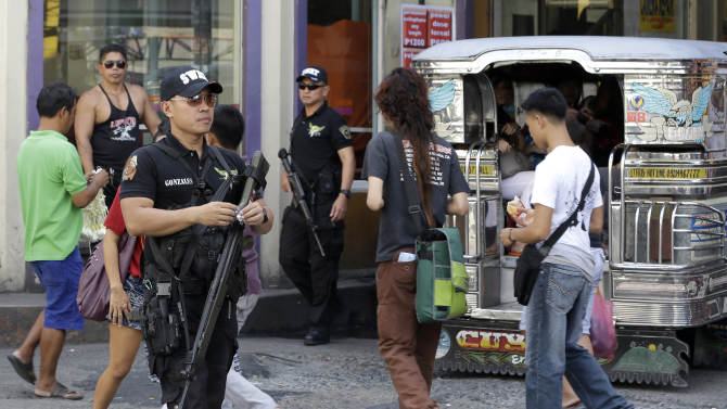 In this Friday Feb. 1, 2013 photo, Pasay city SWAT members of the Philippine National Police make the rounds of business establishments as they go on patrol at suburban Pasay city, south of Manila, Philippines. Security problems are not new to the Philippines - kidnappings and bombings have plagued the south of the country for decades - but the latest rash of violence comes as President Benigno Aquino III tries to shore up foreign investments and restore Filipinos' confidence in their government. (AP Photo/Bullit Marquez)