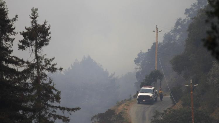 A firefighter walks along the access road to Pfeiffer Ridge during a wildfire in Big Sur